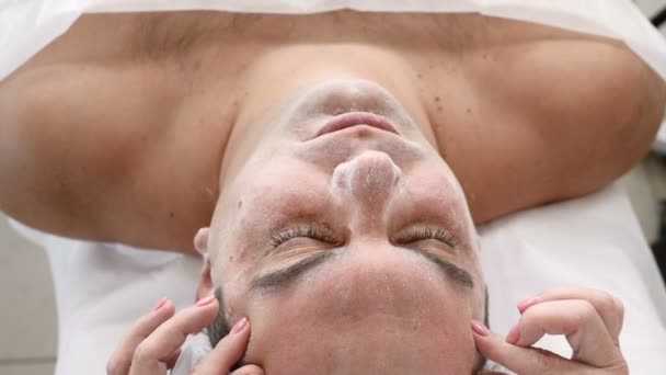 Man in beauty clinic. Male client gets facial cosmetology procedure in beauty salon. Face lymphatic massage