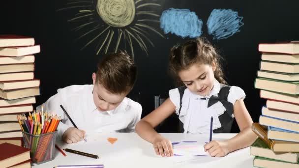 Koncepce školy. Roztomilé děti těšit na ssuccess sedí u stolu s hromadami knih a kreslící tabulí s výkresy za nimi. Vysoké pět. Cíl dosáhnout. 4k