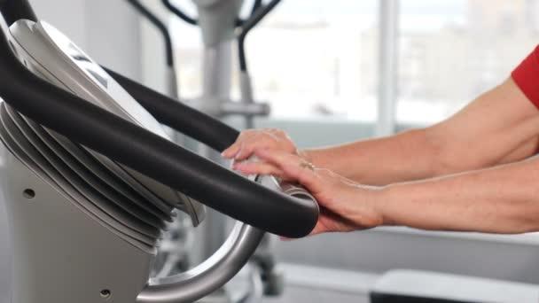 Aktivní starší žena v tělocvičně. Zavřít. Ženské ruce na rukojeti kola ve fitness studiu. Stará žena točí kolo na cyklistické třídě. Fitness starší žena trénink na statické kolo ve sportovním klubu. 4k