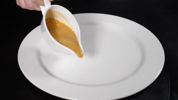 Pouring delicious sauce on white plate. Studio lights. Close up. Cooking food in restaurant. Drawing on white plate. Salad serving. Fine cuisine. Shot in hd