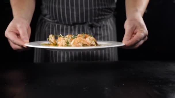 Restaurantkonzept. Koch präsentiert sein Gericht vor Kunden. Nahaufnahme. Restaurant Essen Kochen und Servieren. Küchenchef hält weißen Teller mit gebratenen Garnelen in der Hand und stellt ihn auf den Tisch. Schuss in