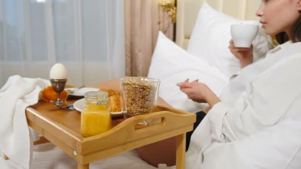 Pohled zezadu mladé ženy oblečené v bílé pánské košili odpočívající v posteli se sněhobílými lůžky, se snídaní na malém stolku-tác. Žena bez tváře si užívá ranní kávu za denního světla. 4k