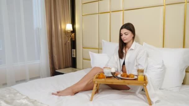 attraktive junge Frau frühstückt morgens im Bett. erfolgreiche Reiserin beim morgendlichen Kaffee im Hotelzimmer. 4k