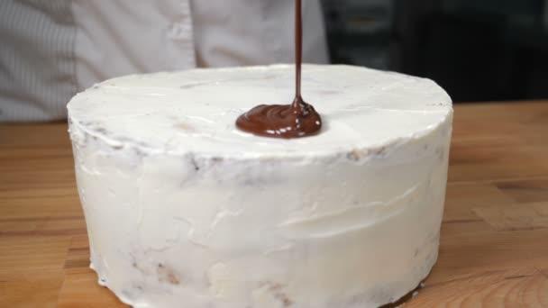 Topping Schokolade Dessert. leckeren Kuchen in weißer Glasur mit heißer Schokolade übergossen. Dekorieren mit geschmolzener Schokolade in Zeitlupe. köstlicher Schokoladenkuchen, der auf einer Holzoberfläche steht. hd
