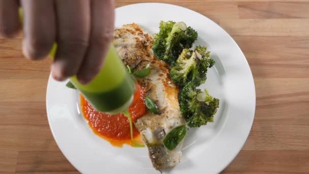 Pohled shora na jídlo se smaženým rybím filé podávané se zelenou brokolicí. Šéfkuchař drží loď s omáčkou. Mouthwatering omáčka se nalévá na talíř. Zpomal. Shot in hd