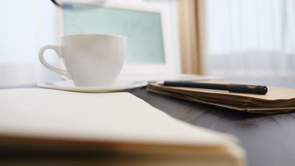 Üzleti koncepció. Közelről. A szemüveget jegyzettömbre teszik. Fehér füzet és egy csésze kávé a háttérben. Szemüveg, toll és üres jegyzetfüzet az irodai asztalon. 4k-ben lőtték le.
