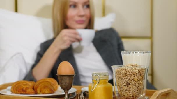 Mladá docela úspěšná podnikatelka snídá v luxusním hotelovém pokoji. Girl in light hotel apartment enjoying coffee at morning time on small table-tray, Shot in 4k