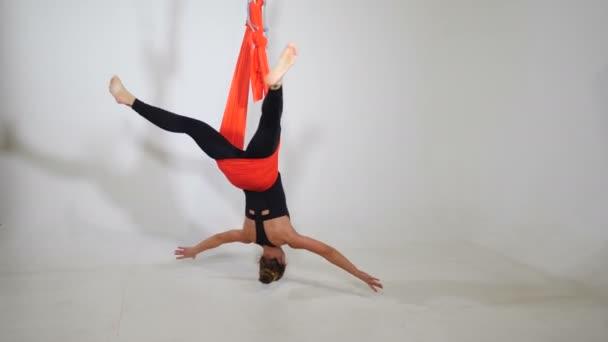 Letecká, antigravitační jóga v tělocvičně. Mladá žena cvičí jógu na bílém pozadí. Fitness sportovkyně visící ve vzdušném prostoru pomocí tkaniny houpací síť uvnitř. Okouzlující ženy se vznášejí ve vzdušném prostoru. výstřel