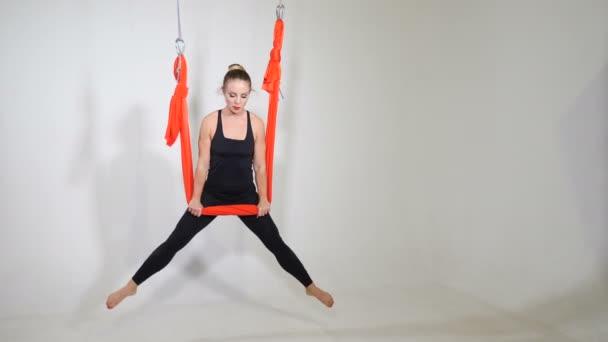 Mladá usměvavá sportovní žena visí v houpací síti na jógu. Životní styl a sport. Letecká jóga. Atraktivní sportovkyně praktikující muškařskou jógu v houpací síti na bílém pozadí. Záběry 4k