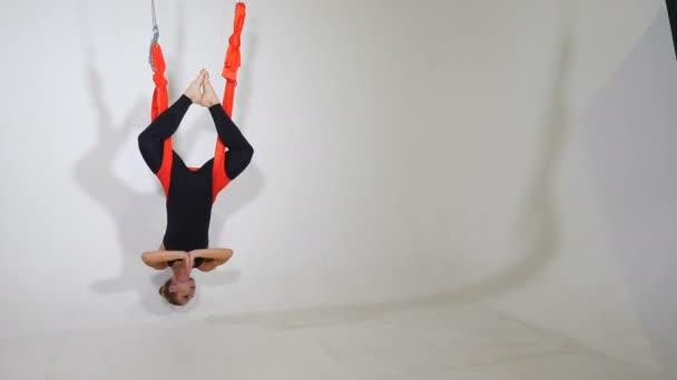 Vonzó sportos nő, aki antigravitációs jógát gyakorol a függőágyas sportklubban, fehér falakkal. Gyönyörű hölgy lebeg a levegőben a padló felett, légi jóga. koncepció sport az életben. 4k videó