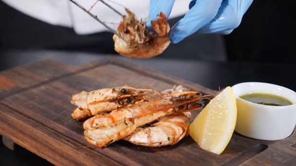 Profesionální kuchař vaří jídlo s hluboce smaženými krevetami. Boční pohled. Koncept jídla v restauraci. Zpomal. Full hd