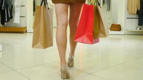 Visszapillantás a divatvásárló nőkre az áruházban, színes táskákkal a kezükben. Alacsony lövés a női lábak séta fényes divat butikban visel színes ruhák vásárlások zsákokban. 4 k videó