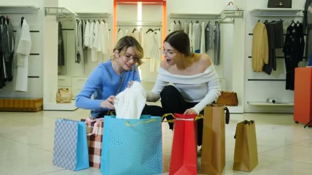 Portrét krásných stylových a módních zákaznic držících stříbrný prodejní nápis v módním butiku a usmívajících se na kameru. Nakupování, slevy a černou ledničku. 4k výstřel