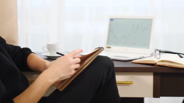 Fiatal nő kezét írásban listát csinál jegyzeteket napló tervezés segítségével napló emlékeztető fényes szállodai szobában. Közelkép. Gyönyörű nő vállalkozó kézírás munka után, és jegyzetel