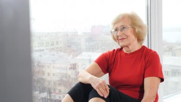 Portrét příjemné ženy v důchodu v tělocvičně. Zdravá a aktivní stará žena. Aktivní maturanti. Stará paní ve fitku. Záběry 4k