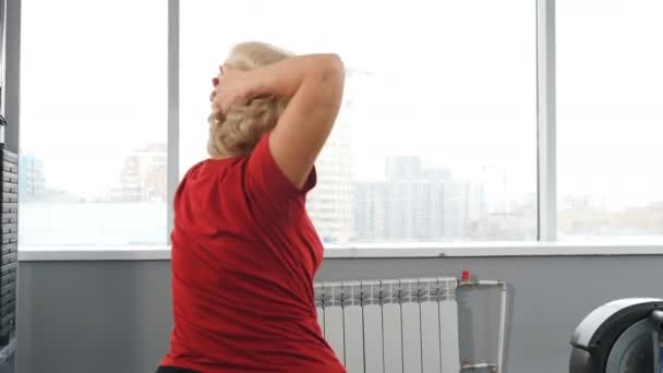 Seniorin beim Training im Fitnessstudio. Rückansicht einer Rentnerin, die auf einem Fitnessball sitzt und im Fitnessstudio trainiert. Konzept der aktiven und gesunden Rentner. Schuss in 4k