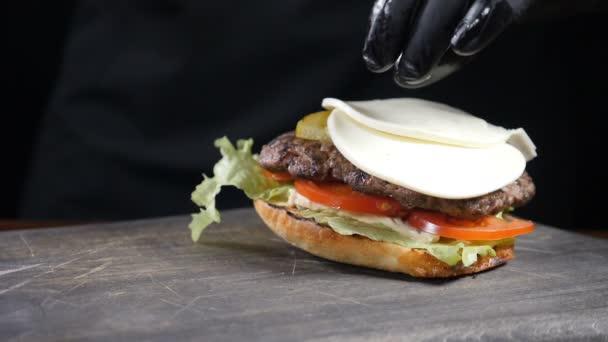 Slow motion Food koncept. Šéfkuchař dělá burger. Detailní záběr. Burger restaurant menu vaření proces. Šéfkuchař připravuje rychlé občerstvení v restauraci, kde nakrájí krájený sýr na grilované maso. Full hd
