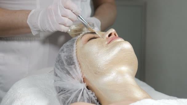 Szépségápoló maszkot visel a gyönyörű női lányok arcán. Kozmetikai arany maszk az arcon az emelő hatás. Egy fiatal nő portréja, amint szépségápolási eljárást kap. Közelkép a szépségszalonban. 4 k