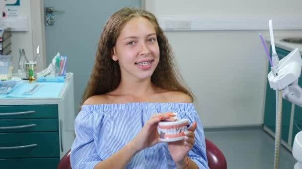 Lächelndes Mädchen mit orthopädischen Zahnspangen im Zahnarztstuhl. Gesundheitswesen, Zahngesundheit und Zahnheilkunde. Glückliche junge kaukasische Mädchen Blick auf Kamera posiert auf Zahnarztpraxis Hintergrund für Video