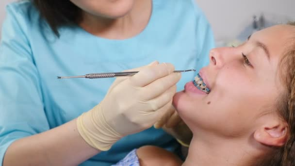 Female orthodontist examining child in dental office. Close-up. Pretty girl with braces on her teeth in modern dental clinic. Orthodontic Treatment. Teeth with dental braces. Bite correction
