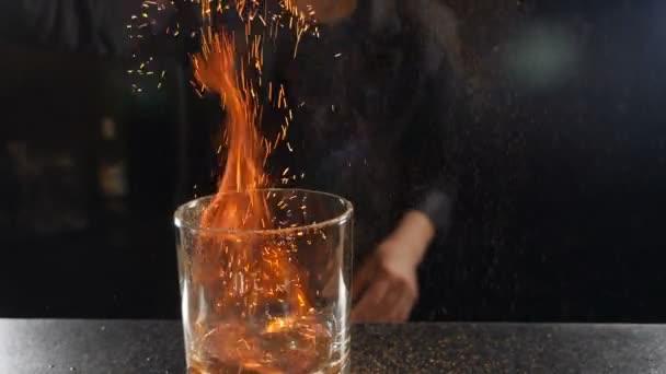 Barkeeper setzt Cocktail in Brand und verbrennt Zimt in Alkoholgetränk auf schwarzem Hintergrund. Flammen im Cocktailglas in Zeitlupe, brennender Zimt im Alkoholgetränk, Barmann trinkt. Full-HD-Filmmaterial
