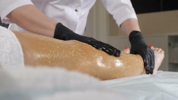 Detailní záběr ženské klientky v salonu krásy, jak dostává kosmetickou péči o pleť, hubnutí a zákrok proti tuku na nohách ve wellness klinice. Kosmetička v černých rukavicích provádí proceduru zábalu těla