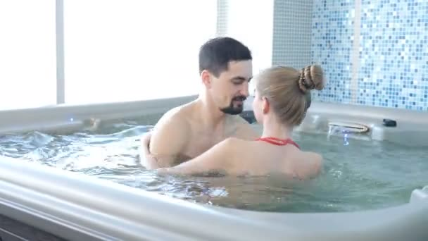 Wellness spa centre in luxury hotel. Couple relaxing in jacuzzi having fun. Attractive slim woman in red bikini swimsuit riding on water waves in pool. 4 k video