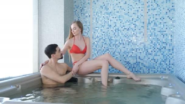 Wellness a lázně - mladý milující pár relaxující u bazénu v hotelových lázních. Šťastná mladá žena a muž odpočívá ve vodě u bazénu na dovolené. Záběry 4k