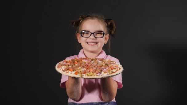 Pretty funny girl holding out ready delicious pizza. Smiling child with tasty pizza on hands. Pizzeria advertising. on black background. slow motion. Full hd