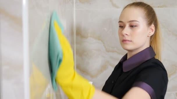 Hausmeisterdienst. Reinigungskonzept. Hausmädchen in Gummihandschuhen waschen Keramikfliesen an der Wand mit einem Lappen und Reinigungsmittel. Junge Frau vom Hotelpersonal in Uniform und Schutzhandschuhen