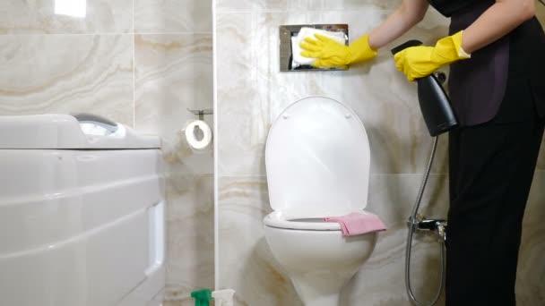 Takarító cég. Krómozott vécécsésze tisztító gomb a fürdőszobában, bidé. polírozó fogantyúk. Takarítás a hotelben. Közelkép a szobalányról a hotel személyzetéből, amint a fürdőszobát törölgeti a lakásban.