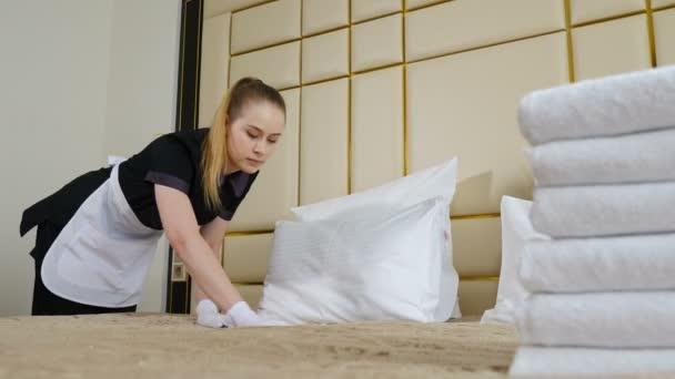 Koncept hotelu. Mladá, krásná služebná v uniformě a zástěře, ustlaná v pokoji, prostřílená hromadou čistých ručníků na prostěradle. Příprava hotelového pokoje. 4 k video