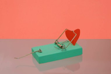 Mousetrap mint color on coral surface. Red heart made of coarse paper in a mousetrap. Copy space.
