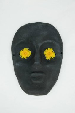 Black ceramic mask on a white background. Yellow dandelion flowers in the eyes of a mask. Mass produced mask. Copy space.