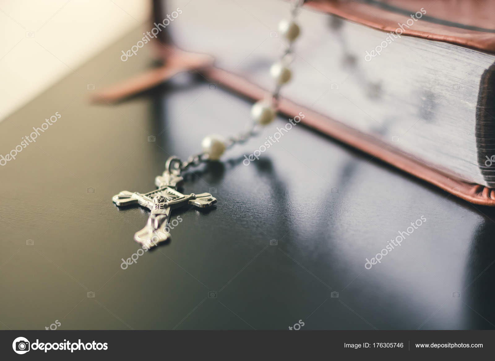 A Closed Brown Leather Bible Is Set On A Black Shiny And Reflective Table  Top. Hanging Over The Bible Is A Silver And Pearl Rosary Necklace. The  Crucifix ...