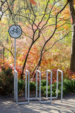 Bicycle metal parking of gray pipes, with parking sign, in the autumn park near beautiful trees and bushes