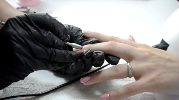 Manikérka otírá nehty, hýbe kůžičkou s tlačenicí a přikrývá nehty