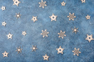 Winter flat lay with wooden snowflakes on a blue textural background. Concept for Christmas and New Year.