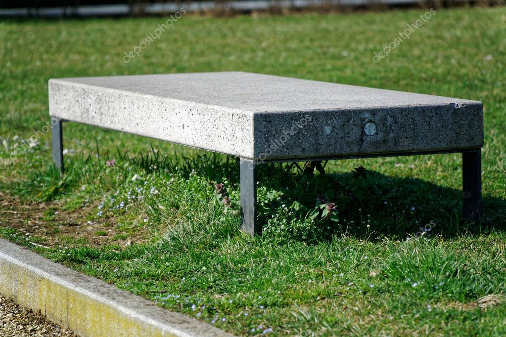 Stone granite bench in public park, place for relaxing