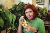 Fotografie Nette junge Frau Essen ein Eis im café