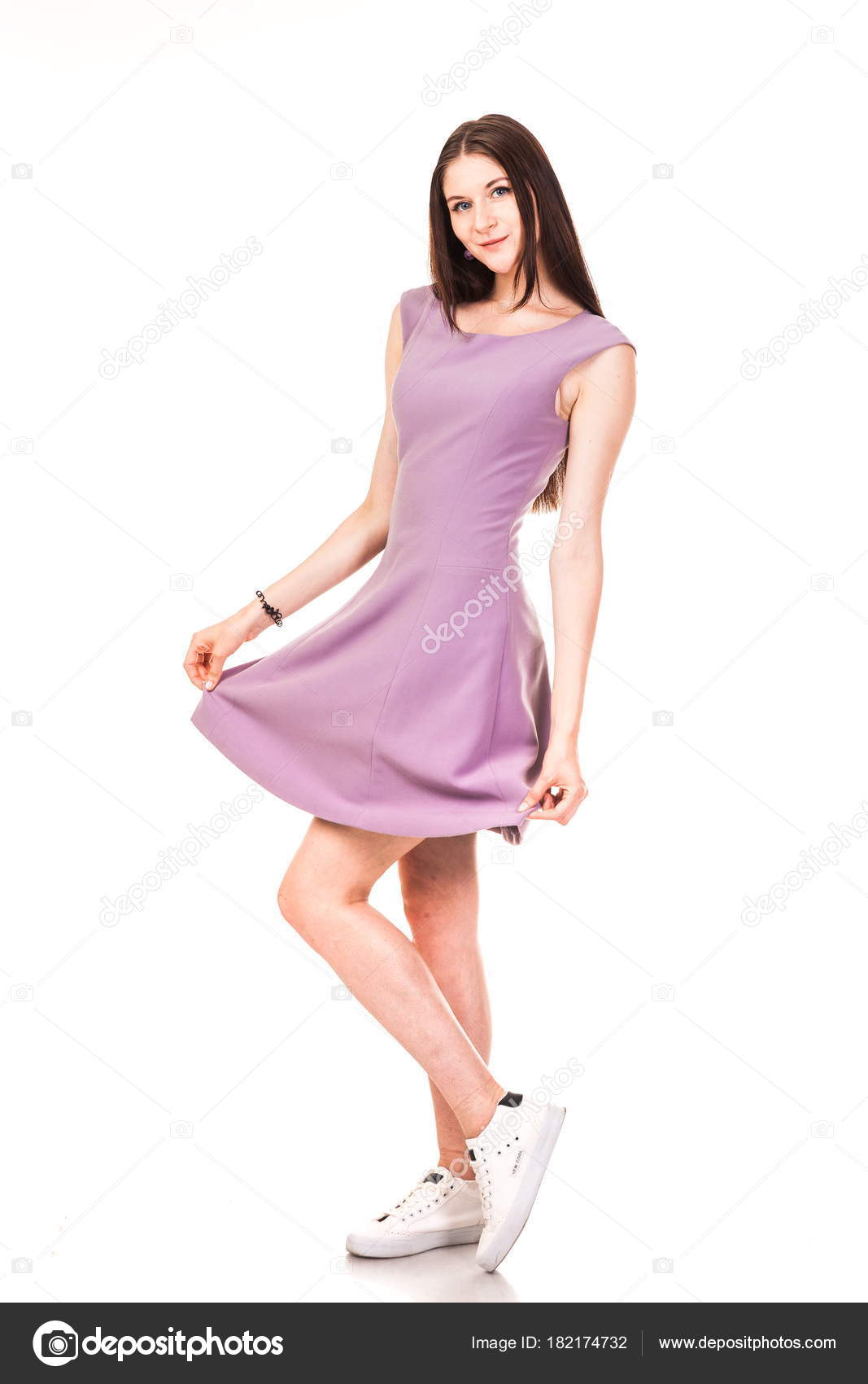 8f70827d195fc5 Mooie jonge meisje in roze jurk en sneakers. Een foto op een witte  achtergrond
