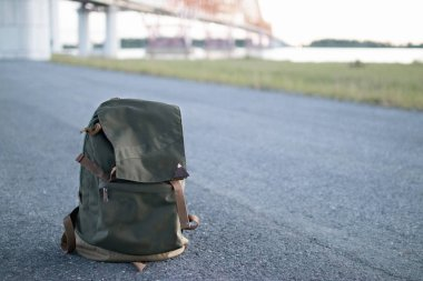 Backpack on the road in front of a river and bridge