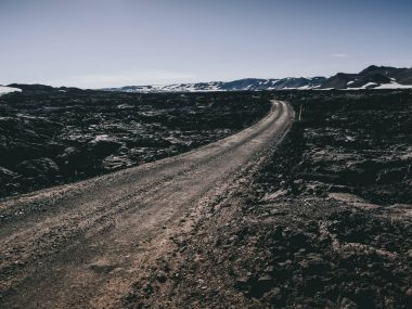 scenery with road and black rocks and mountains in Iceland