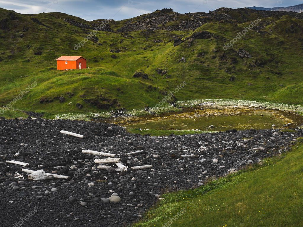 northern landscape with lone red house in green mountains, Iceland