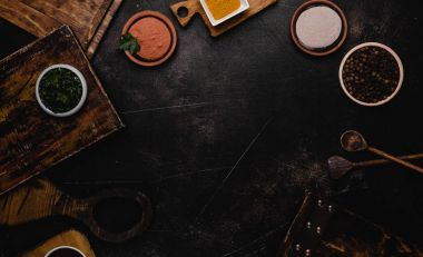 top view of wooden cutting boards and spices on black surface