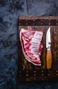 top view of raw beef ribs on wooden board with knife