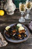 gekochte Muscheln mit Muscheln auf Teller serviert mit zwei Gläsern Weißwein auf Holztisch