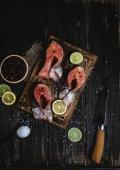 a rusztikus, fából készült asztal friss szeletelt piros hal, a fűszereket és a késsel citrusfélék szelet felülnézet