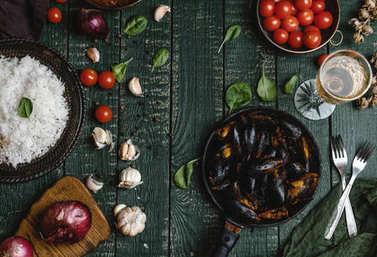 Top view of cooked mussels with shells served in pan with tomatoes, herbs and wine on wooden table