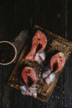 top view of sliced fresh salmon on wooden cutting board with sackcloth, salt and peppercorns on rustic table